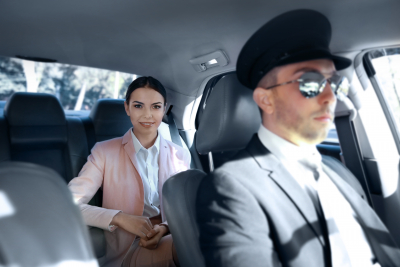 chauffeur driving car with woman on back seat